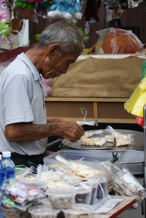 An old asian man selling packed finger food at roadside hawker stand