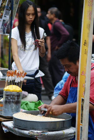 Asian man preparing ting ting candy  gula ketuk  at the roadside hawker stand