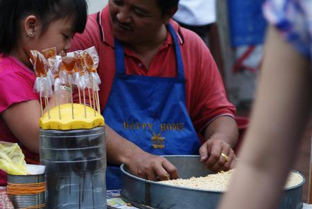 roadside stand: Asian man preparing ting ting candy  gula ketuk  at the roadside hawker stand Editorial