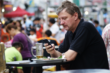 Caucasian man playing with his phone while having lunch at a roadside hawker stall