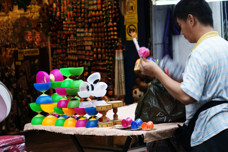 Asian man selling yoyo at roadside hawker stand