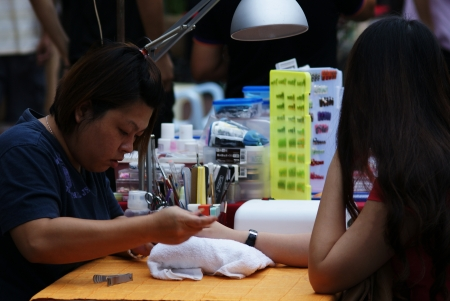 Asian manicurist lady doing manicure for a customer at a nail salon