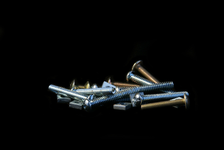 Set of multi sizes machine screws with square nuts isolated on black background photo