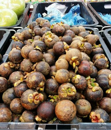 Mangosteen fruits piled for retail at the market Stock Photo