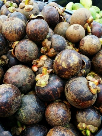 sold small: Mangosteen fruits piled for retail at the market Stock Photo