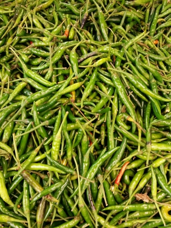 eye: Very hot green birds eye chilli or cili padi piled for retail at the market Stock Photo