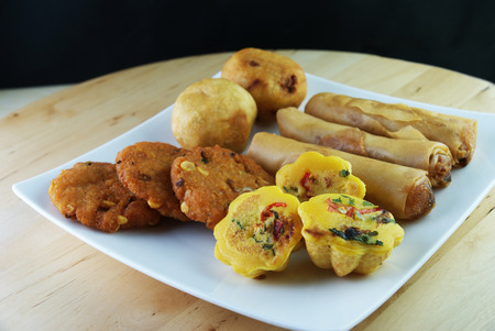 Assorted Malay traditional food on a white plate - Kuih Cara Berlauk, Cucur Badak, Popiah, Vadeh