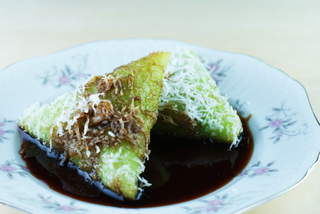 Malay traditional food - Kuih Lopes, pandan flavoured glutinous rice with palm sugar syrup photo