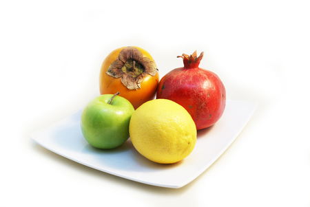 Four pieces of colourful fruits on white plate - Lemon, Granny Smith Green Apple, Pomegranate, Hachiya Persimmon photo