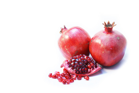 Two whole and a cut open ripe Pomegranate fruit or Buah Delima