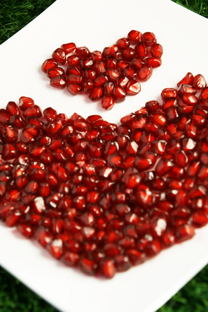 Loose pieces of Pomegranate fruit or Buah Delima spread into heart shape on a square white plate