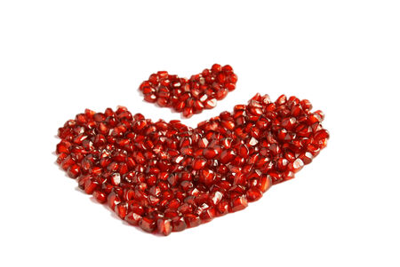 Loose pieces of Pomegranate fruit or Buah Delima spread into heart shape