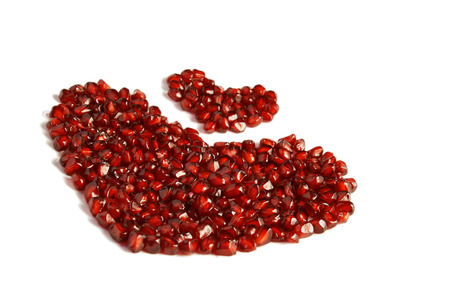 Loose pieces of Pomegranate fruit or Buah Delima spread into heart shape photo