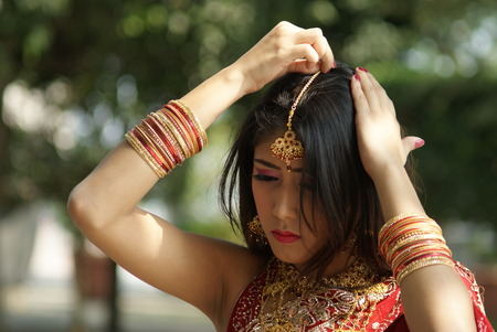 Young Indian girl in red traditional saree clothing fixing her hair pin