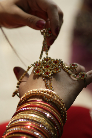 Young Indian girl wearing bangles and hand ring piece decoration Stock Photo