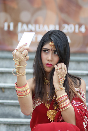 Young Indian girl in red traditional saree clothing taking a selfie with her white phone