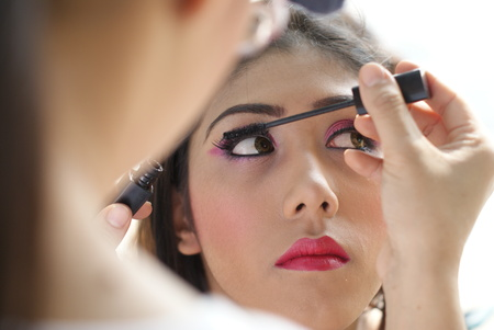 Young Indian girl having her face makeup done photo