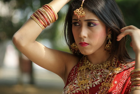 Young Indian girl in red traditional saree clothing