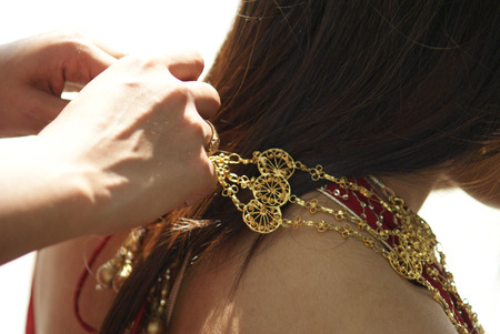 Young Indian girl in red traditional saree clothing fixing her necklace