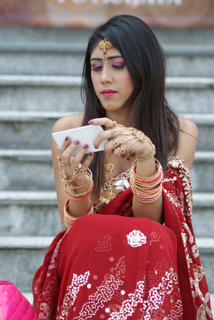 Young Indian girl in red traditional saree clothing with a white phone