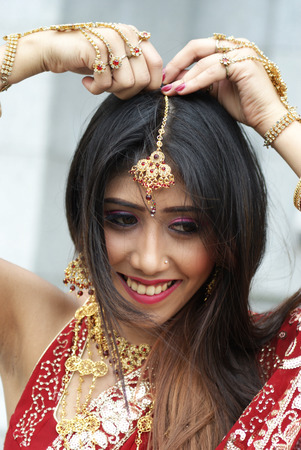 Young Indian girl in red traditional saree clothing fixing her hair pin photo