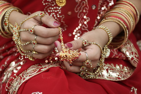 Young Indian girl in red traditional saree clothing holding a hair pin in her hand