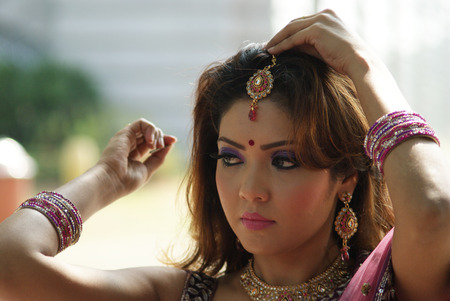Young Indian girl in purple traditional saree clothing fixing her hair pin Stock Photo