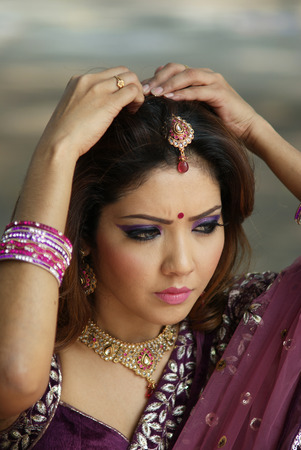 Young Indian girl in purple traditional saree clothing fixing her hair pin photo