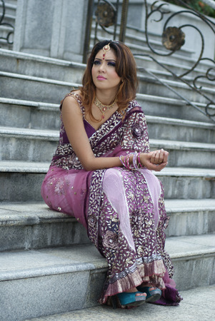 Young Indian girl in purple traditional saree clothing at stairs