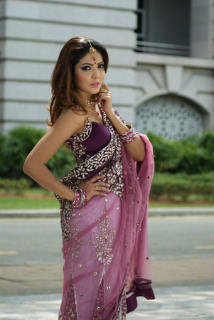 Young Indian girl in purple traditional saree clothing