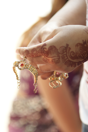 Indian girl with henna painted hand holding hand accessory