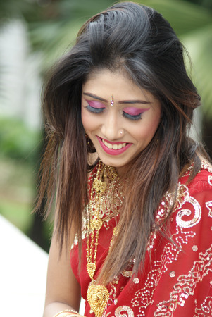 Young Indian girl in red traditional saree clothing facing down with her eyes closed