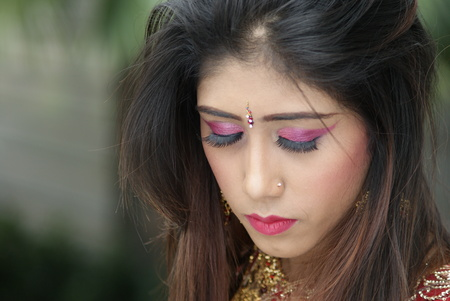 Young Indian girl in red traditional saree clothing with her eyes closed photo