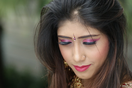 Young Indian girl in red traditional saree clothing with her eyes closed Stock Photo