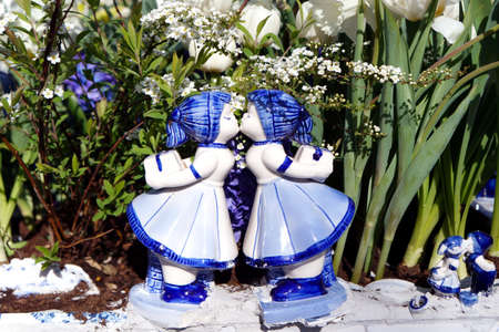 porcelain flower: Porcelain figures in flower bed Stock Photo