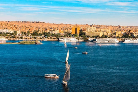 egypt pyramid: Sailboats sliding on Nile river  Felluca  traditional boat  of Egypt in Aswan s sunset