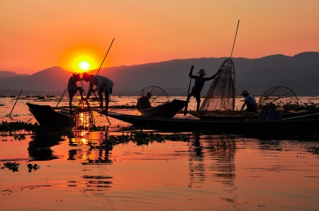 fisherman boat: Fishermen in Inle lakes sunset Fishermen is finish a day of fishing in Inle lake, Myanmar  Burma   Inle is one of the most favorite tourist places in Myanmar  Burma  Stock Photo