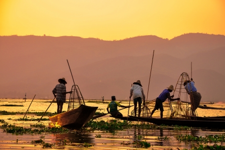 inle: Fishermen in Inle lakes sunset Fishermen is finish a day of fishing in Inle lake, Myanmar  Burma   Inle is one of the most favorite tourist places in Myanmar  Burma  Stock Photo