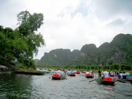 paddler: NINH BINH, VIETNAM, JULY, 20: Unidentified tourists in Trang An  on JULY, 20, 2013. Trang An is the scenic area, ranked special of Vietnam Editorial