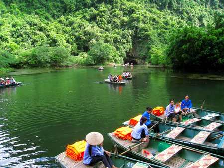 paddler: NINH BINH, VIETNAM, JULY, 20: Women rowing in Trang An on JULY, 20, 2013. Trang An is the scenic area, ranked special of Vietnam.
