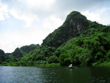 paddler: NINH BINH, VIETNAM, JULY, 20: Unidentified tourists in Trang An  on JULY, 20, 2013. Trang An is the scenic area, ranked special of Vietnam.