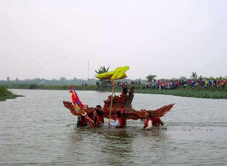 palanquin: HAI DUONG, VIETNAM, December, 9: Group of people in traditional costume palanquin procession holy wading into the river at Kien Lao temple festival on December, 9, 2012 in Hai Duong, Vietnam. palanquin procession of holy is the sacred ceremonie of festiva