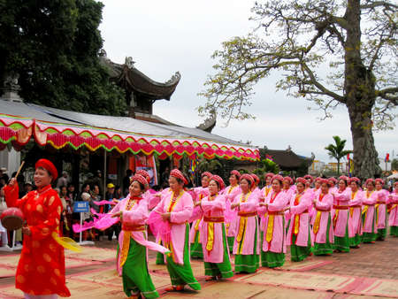 HAI DUONG, VIETNAM, March 29: group of people in traditional costumes and fan arrange letters in the new year for luck at Mao Dien temple on March, 29, 2013 in Hai Duong, Vietnam. This is the beauty of Vietnam to honor the learning.