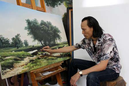 HAI DUONG, VIETNAM, July, 25: the artist is drawing la landscape painting in his studio on July, 25, 2013 in Hai Duong, Vietnam.  Redactioneel