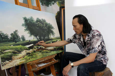 HAI DUONG, VIETNAM, July, 25: the artist is drawing la landscape painting in his studio on July, 25, 2013 in Hai Duong, Vietnam.