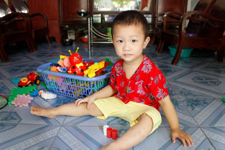 HAI DUONG, VIETNAM, September, 10: Asian boy about 1 year old, alone , playing with toys on September, 10, 2013 in Hai Duong, Vietnam.