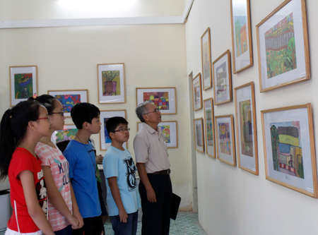 HAI DUONG, VIETNAM, September, 13: old man and teens watch picture exhibition on September, 13, 2012 in Hai Duong, Vietnam