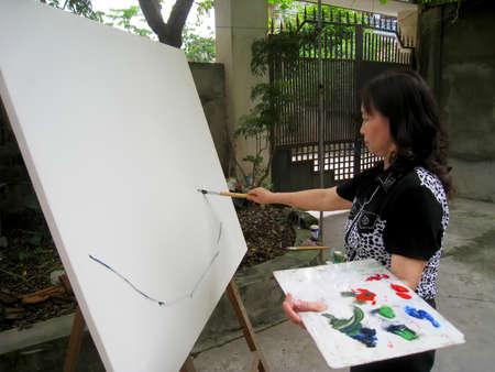 HAI DUONG, VIETNAM, September, 13: female artist painting at home on September, 13, 2012 in Hai Duong, Vietnam