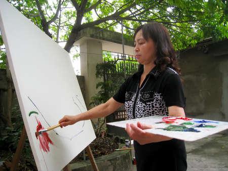 adult vietnam: HAI DUONG, VIETNAM, September, 13: female artist painting at home on September, 13, 2012 in Hai Duong, Vietnam Editorial