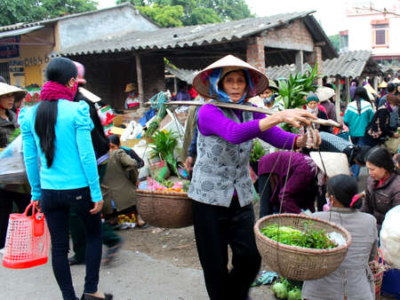 HAI DUONG, VIETNAM, April, 2: Asian woman selling vegetables at the market on April, 2, 2014 in Hai Duong, Vietnam.